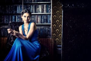 Beautiful young woman sitting in a library with a blue evening dress