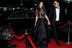 Glamorous young couple walking up the red carpet in formal evening wear